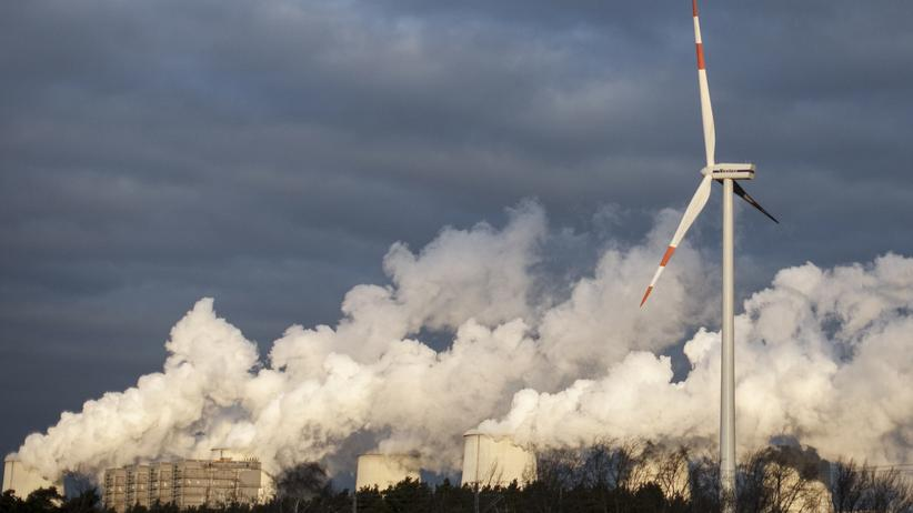 Klimaschutz: Windkraftanlage vor den Kühltürmen eines Kohlekraftwerks in Jänschwalde