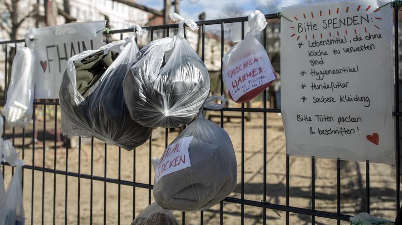 Weitere Maßnahmen für Berlin : Tüten mit Kleidung und Essen für die Obdachlosen hängen in einem Park in Friedrichshain.
