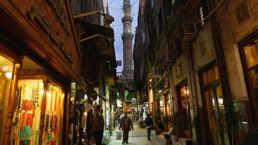 Das Minarett einer Moschee überragt den nächtlichen Basar