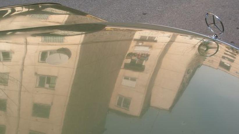 Häuserblocks spiegeln sich in der Motorhaube eines Autos