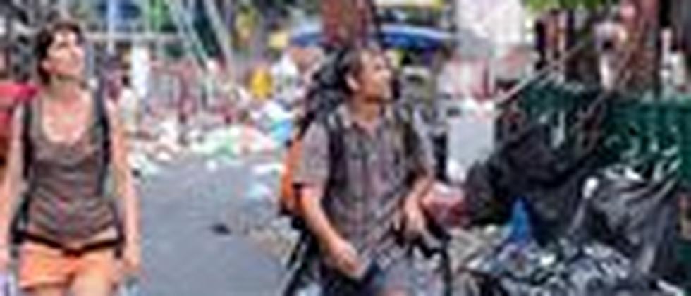 Touristen laufen durch das während der Unruhen zerstörte Stadtviertel