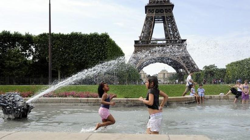 Städtereise: Kinder spielen in einem Brunnen vor dem Eiffelturm in Paris