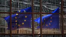Flaggen spiegeln sich im Fenster des EU-Paraments in Brüssel