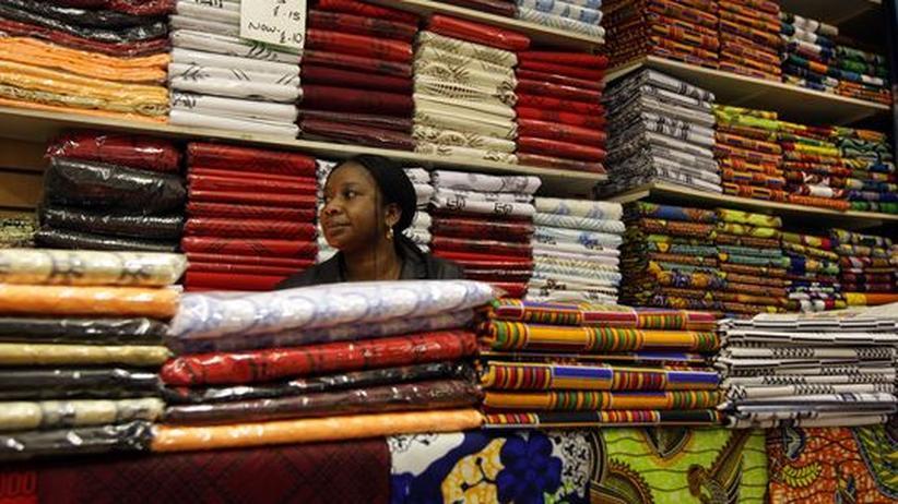 Eine Händlerin sitzt inmitten ihrer Tücher und Stoffe