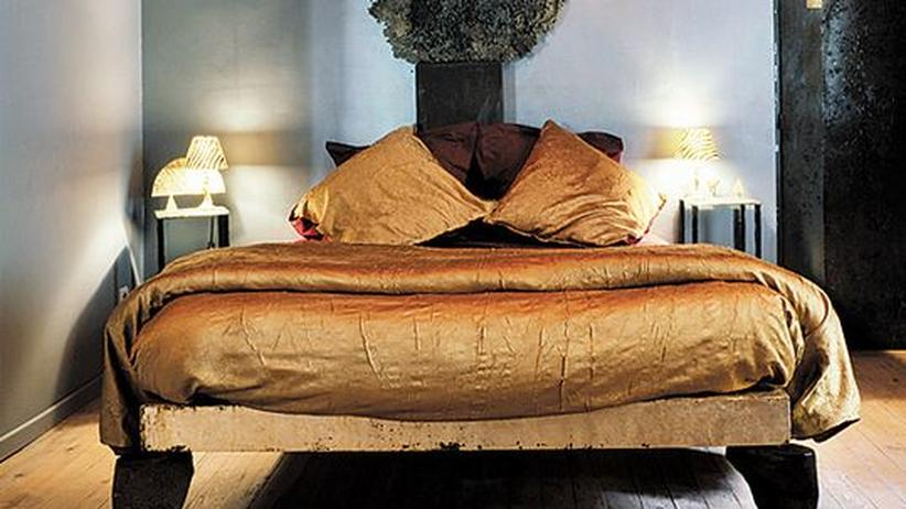 Im Zimmer liegen goldene Decken auf Betten aus Stahl