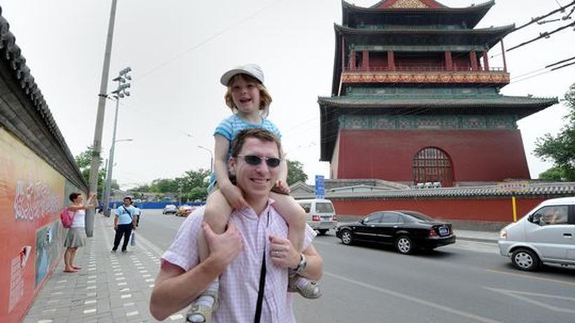 Ein Vater trägt sein Kind in Peking auf den Schultern