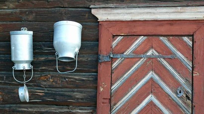 Zwei Milchkannen hängen neben einer Tür