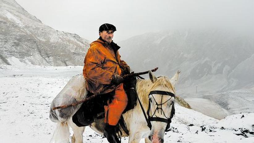 Der alte Mann in Orange leitet vom Pferd aus einen der Trekks