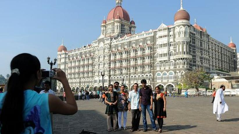 Eine indische Familie lässt sich vor dem Taj Mahal Palace Hotel fotografieren