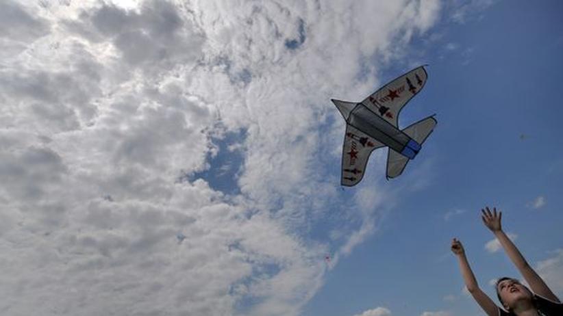 Ein Junge lässt einen Drachen in Form eines Flugzeugs steigen