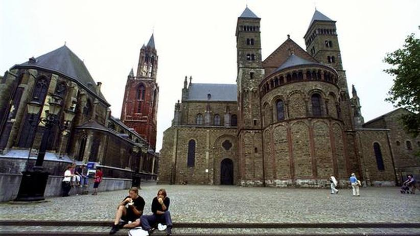Jugendliche sitzen vor der Saint Jans Kirche und der Basilika Saint Servaas in Maastricht