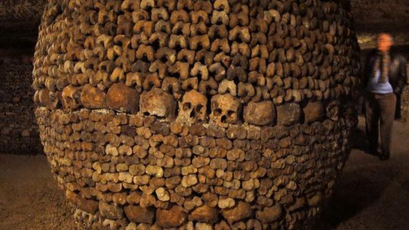 Ein Besucher betrachtet eine Säule aus Knochen. Aus Platzmangel auf den Friedhöfen wurden die Gebeine der Pariser gegen Ende des 18. Jahrhunderts in den Katakomben untergebracht