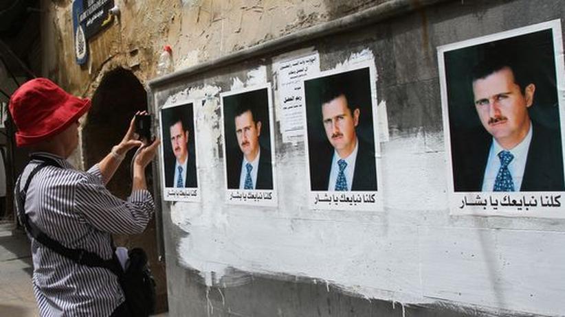 Eine Touristin fotografiert in der Altstadt von Damaskus Plakate mit dem Bild des syrischen Präsidenten Baschar al-Assad.