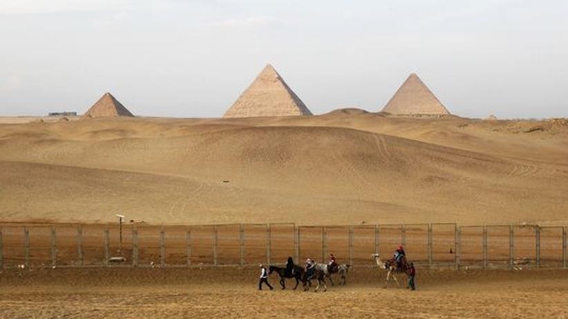 Ägypten-Reisen: Die Pyramiden von Gizeh. Einheimische führen eine Touristengruppe vorbei.