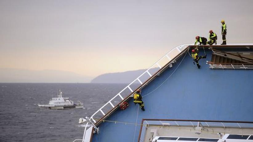 """Kreuzfahrten und Sicherheit: Feuerwehrmänner seilen sich vom Deck des Kreuzfahrtschiffes """"Costa Concordia"""" ab."""