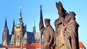 Zwei Wahrzeichen Prags: Hinter den Statuen der Karlsbrücke ragt die Burg auf.