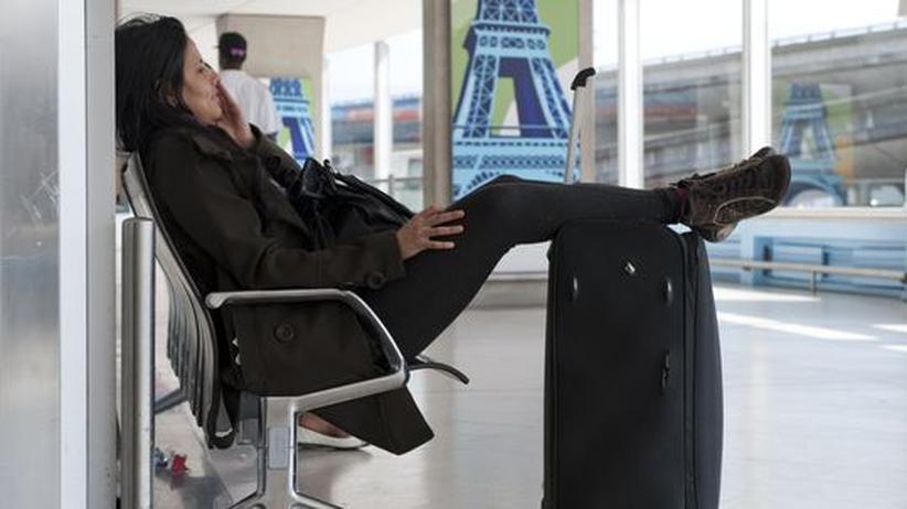 Eine Frau wartet im Flughafen Charles de Gaulle auf ihren Flug.
