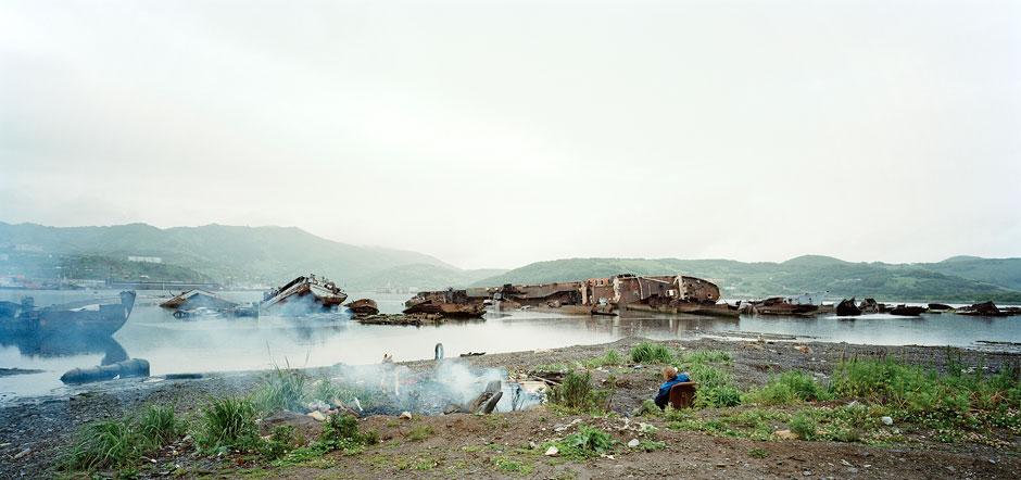 Unbeeindruckt vom aufziehenden Schlechtwetter sammelt eine Frau Treibholz, um ein Feuer zu machen. Schiffsfriedhof. Petropawlowsk-Kamtschatski. Halbinsel, Kamtschatka. Russland 2010