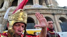 Männer in Centurio-Uniformen posieren vor dem Kolosseum in Rom für Touristen.