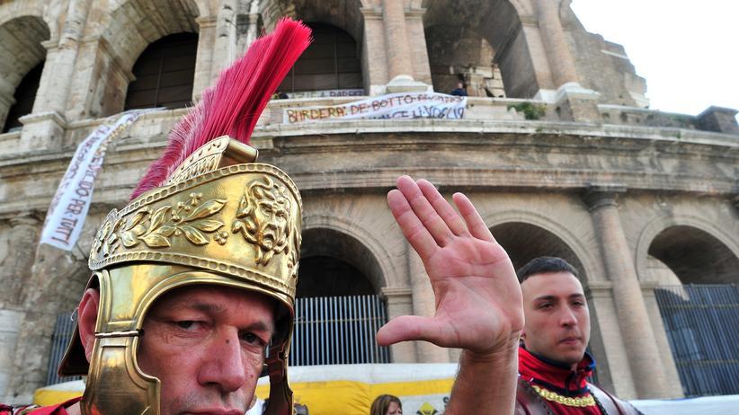 City Guide Rom: Männer in Centurio-Uniformen posieren vor dem Kolosseum in Rom für Touristen.