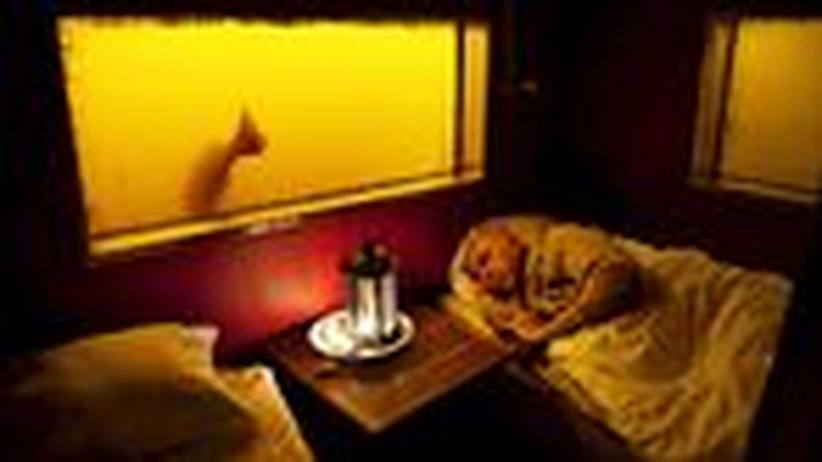 Schweden: Das Zimmer unter der Hütte: Zwei Betten, ein Nachttisch, puffrote Wände.