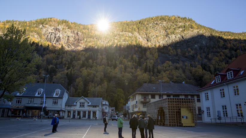 Menschen in einem Sonnenflecken vor dem Rathaus