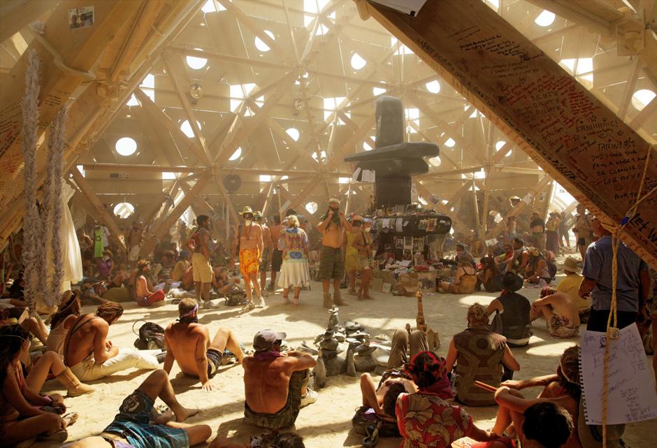 """The Temple of Whollyness, 2013, von Gregg Fleishman, Lightning Clearwater III und Melissa Barron. Teilnehmer im Tempel. Die Steinskulptur aus schwarzem Basalt von Jael La Femina ist ein """"inuksuk"""", inspiriert von Steingebilden der Inuit."""