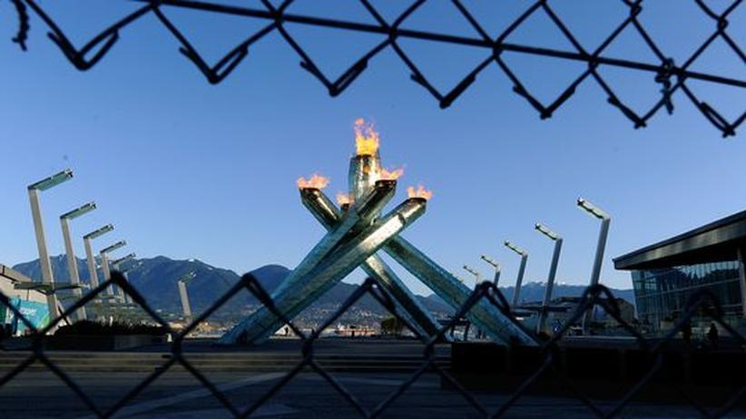Olympia-Gastgeber: Olympische Flamme hinter einem Maschendrahtzaun. Ein Anblick, der Kritik hervorrief