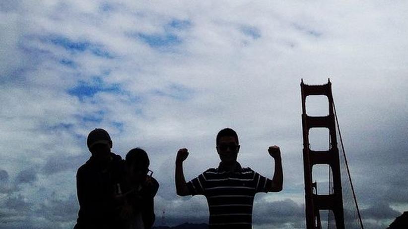 Ein Tourist zeigt vor der Golden Gate Bridge seine Muskeln.
