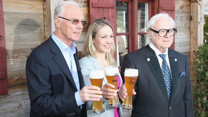 Franz Beckenbauer trinkt im März 2013 neben Magdalena Neuner ein Weißbier.