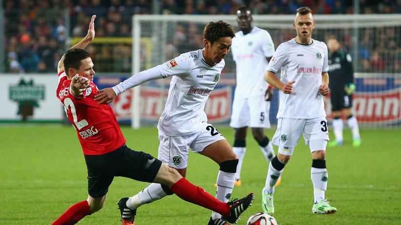 Der Hannoveraner Hiroshi Kiyotake und Sascha Riether vom SC Freiburg kämpfen um den Ball.