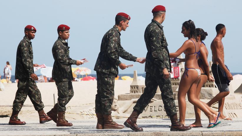 Zika und Olympia: Rio handelt, wie meist, symbolisch: Soldaten klären Badegäste an der Copacabana über Zika auf.