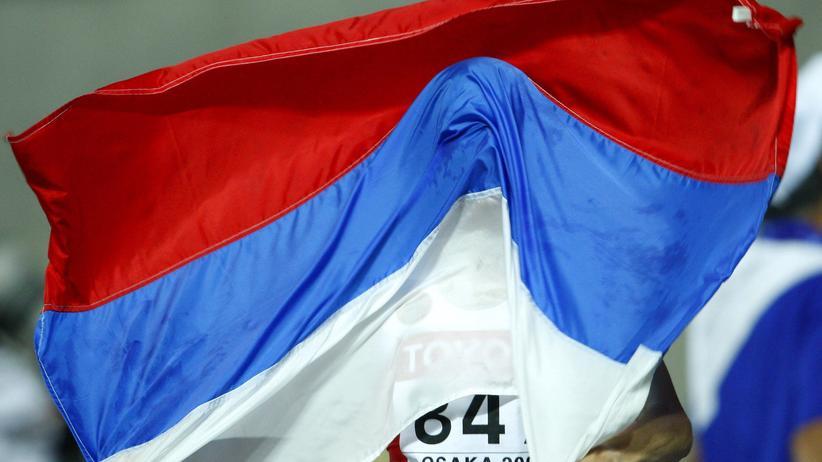 Olympische Spiele: Unter der russischen Fahne verbirgt sich die unter Doping-Verdacht stehende Läuferin Jekaterina Volkova nach ihrem Sieg über 3.000 Meter Hindernis bei der Leichtathletik-Weltmeisterschaft 2007 in Osaka.