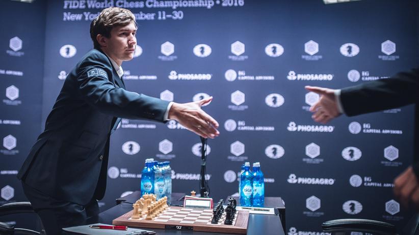 Schach-WM: Sergej Karjakin erhebt sich zum Händedruck mit dem gerade eintreffenden Magnus Carlsen.