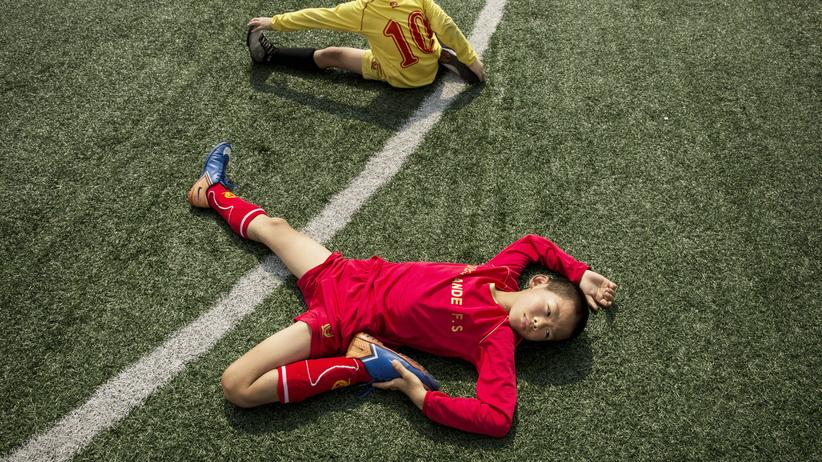 Nachwuchsspieler der Evergrande Football School, der größten Fußballakademie der Welt, dehnen sich vor dem Training.