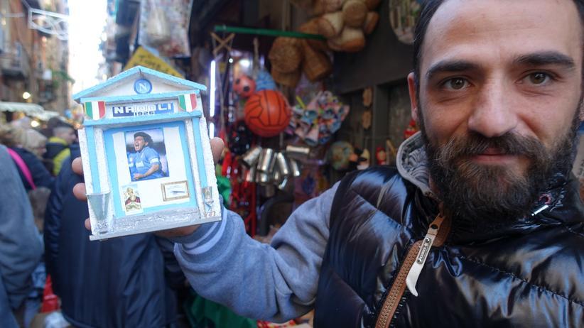 Ein Straßenverkäufer mit einer Maradona-Statue.