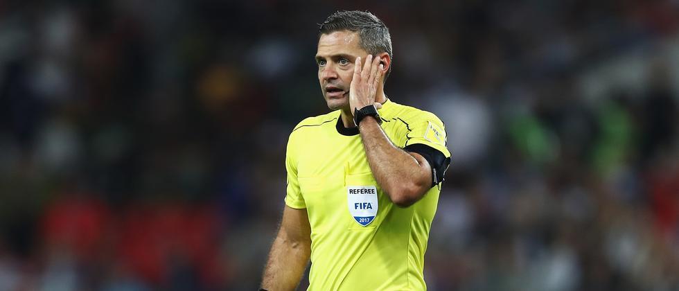 Schiedsrichter Damir Skomina hört zu, was ihm der Videoschiedsrichter während des Spiels Chile gegen Kamerun einflüstert.