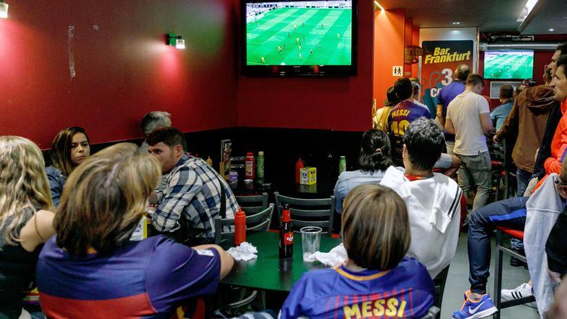 La-Liga-App: Fußballfans schauen nahe des Camp Nou in Barcelona eine Übertragung.