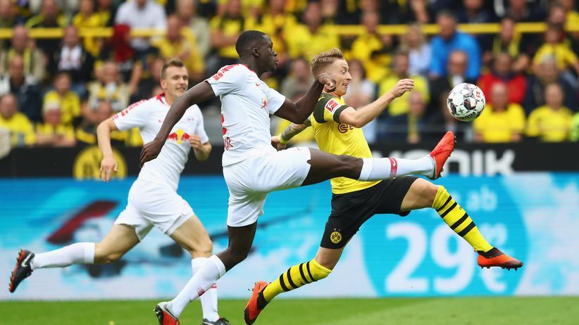 Bundesliga, 1. Spieltag: Dortmunds Stürmer Marco Reus (rechts) bemüht sich gegen Ibrahima Konaté (Mitte) vom RB Leipzig um den Ball.