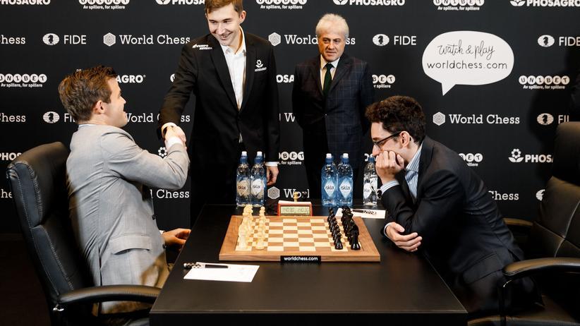 Schach-WM: Vor der 11. Partie der Schach-Weltmeisterschaft in London begrüßt Magnus Carlsen (links) den unterlegenen Herausforderer von 2016, Sergej Karjakin, während Fabiano Caruana (rechts) schon aufs Brett blickt.