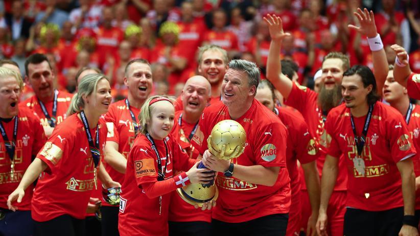Handball-WM: Dänemarks Trainer Nikolaj Jacobsen und sein Sohn stemmen den WM-Pokal.