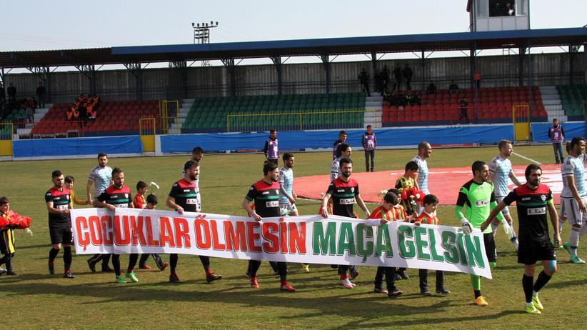 """Fußball in der Türkei: Das Team von Amedspor trägt 2016 ein Banner auf dem steht: """"Die Kinder sollen nicht sterben, sondern ins Stadion."""""""