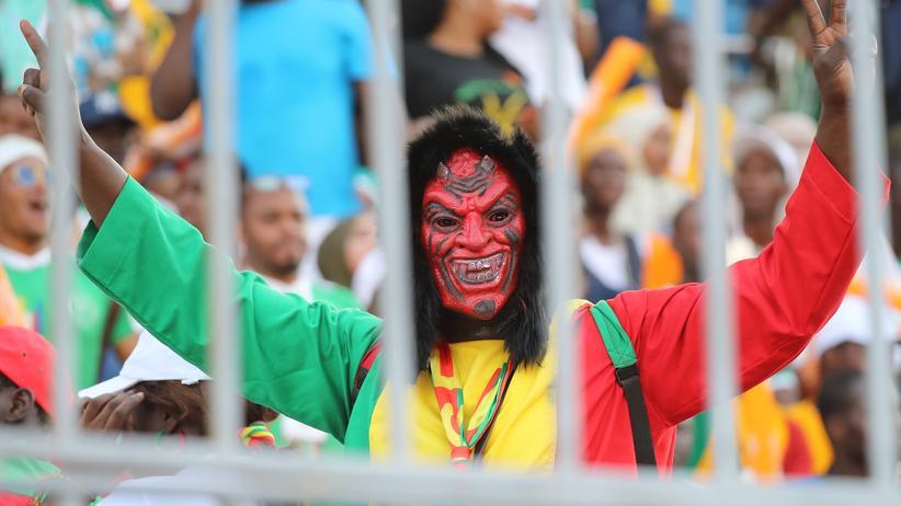 Afrika Cup: Ein Fan aus dem Senegal feiert sein Team. Sie spielen das Finale gegen Algerien. China guckt zu.