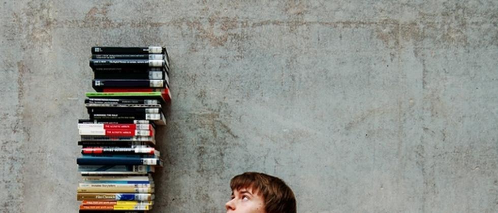 Ein Student sitzt vor einem Stapel Bücher