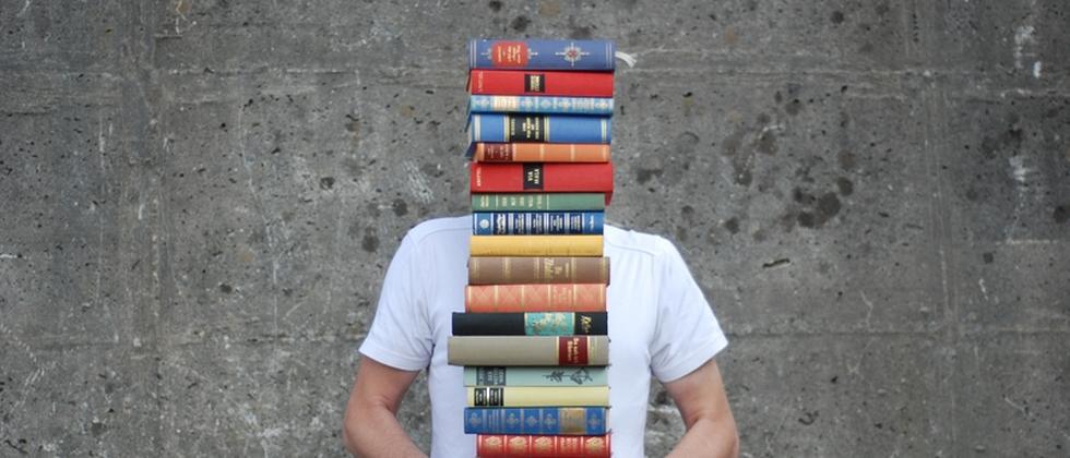 Ein Mann trägt einen Stapel Bücher
