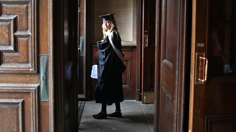 Eine junge Frau trägt die Robe für Doktoranden
