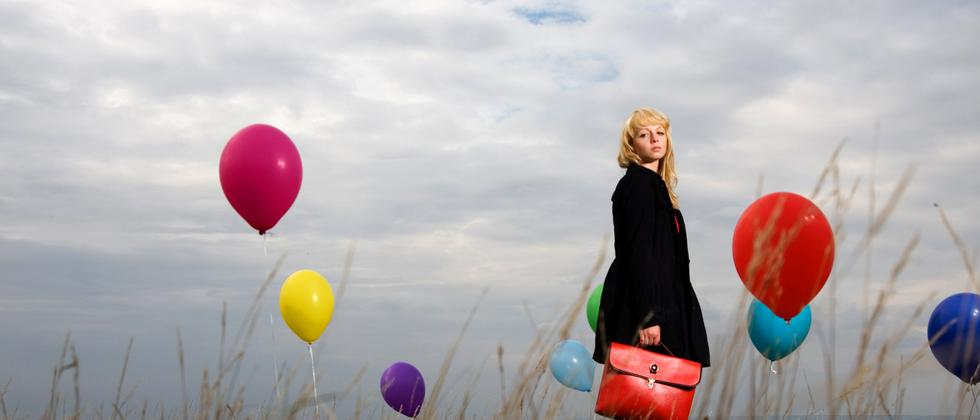 Junge Frau steht in einem Kornfeld mit Luftballons