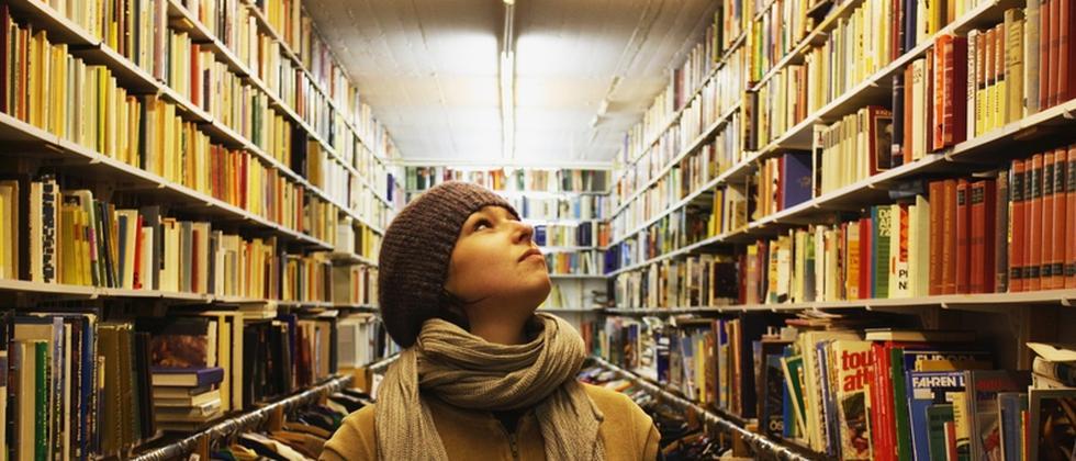 Eine Studentin zwischen zwei Bücherregalen