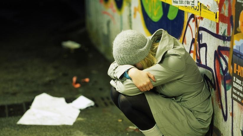 Eine Frau lehnt an einer Wand