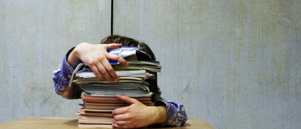 Ein Student hinter einem Stapel Bücher